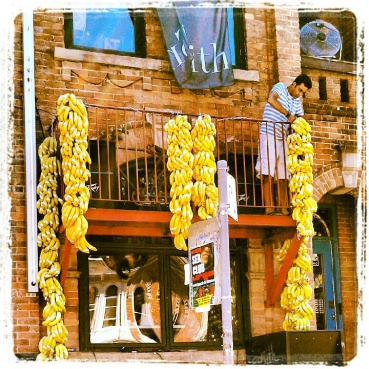 A man working at a club/bar on Church Street hanging bananas on their balcony and patio in preparation for the last day of Pride Week in Toronto