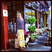A fashionably dressed woman and her adorable dog waiting outside Cafe de la Presse