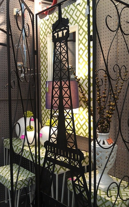 A patterned mirror and nesting tables seen behind an Eiffel Tower room partition.