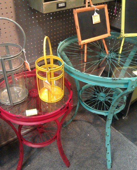 Tables that look to be made out of vintage wire wheels, painted bright colours.