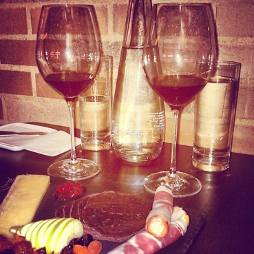 Glasses of Italian red wine and our cheese and charcuterie board on my second visit.