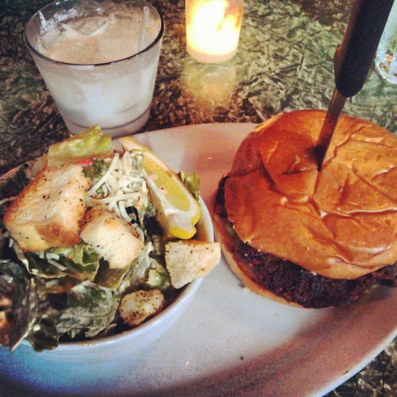 The veggie burger with a side of caesar salad and a coconut caipirinha cocktail.