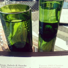 The beautiful emerald green wine bottle water glasses.