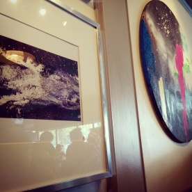 A couple pieces of art hanging on the wall of The Next Act. All were for sale.