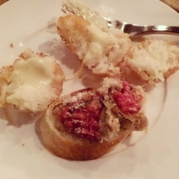 A broken arancini filled with Fontina cheese and roasted cauliflower, and a slice of crostini topped with salumi and shaved truffle.