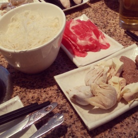 A bowl of vermicelli noodles along with sliced sirloin beef, dumplings, wontons and beef balls.