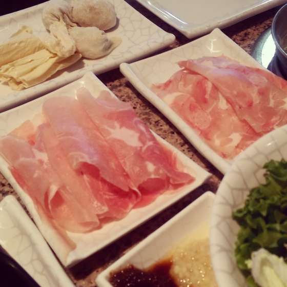 Raw chicken and pork slices, bean curd, dumplings and sauce.