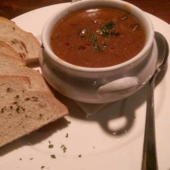 A bowl of the hearty beef goulash with slices of rye bread.