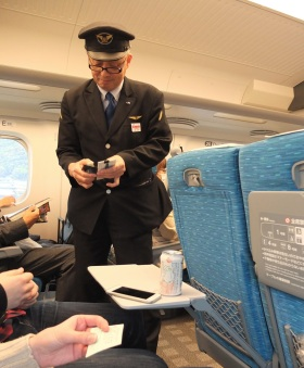 Checking tickets on the bullet train to Kyoto.