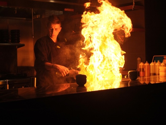 A chef lighting up the teppan grill.