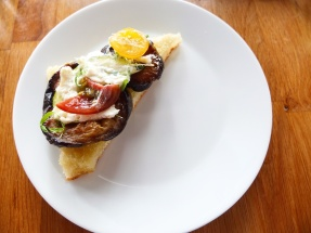 A focaccia triangle topped with ricotta and roast eggplant, zucchini and tomatoes.