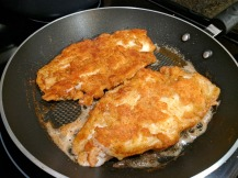 The battered sole being pan-fried.