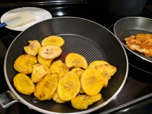 Frying up the slices of plantain.