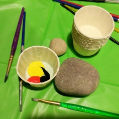 Brushes and paints are provided to decorate river rocks.
