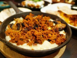 Queso Fundido topped with chorizo and mushrooms.