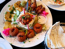 Half Mezza Platter with Falafel, Grilled Halloume Cheese, Chicken Wings, and Sujuk over Hummus