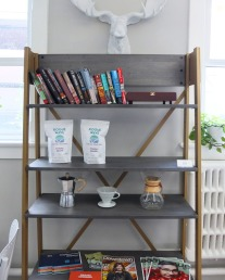 A shelf with a few products as well as books and magazines to read.